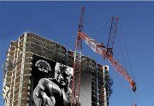 Powerhouse Gym Man Lifting Billboard Ad Talk Cock Sing Song